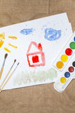 Brush and colorful paints on a child`s picture royalty free stock images