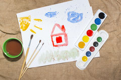 Brush and colorful paints on a child`s picture stock photography