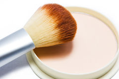 Brush and compact powder beige color isolated on white background. Royalty Free Stock Images
