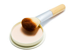 Brush and compact powder beige color isolated on white background. Royalty Free Stock Photos