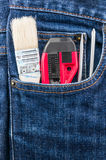 Brush, cutter and screwdriver in blue jean pocket Stock Photos