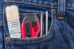 Brush, cutter and screwdriver in blue jean pocket Stock Photo