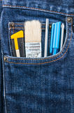 Brush, cutter and screwdriver in blue jean pocket Royalty Free Stock Photos