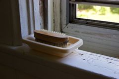 Brush, dish on white windowsill corner with chipped paint, screen Royalty Free Stock Photography