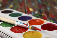 A brush dyed in red paint lies on a set of watercolor paints. Close-up. Sharpness on the tip of the brush. Stock Photos