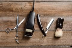 Brush and electric hair trimmer. Scissors, an electric hair trimmer, a brush and a straight razor on the wooden boards background, a top-view image. Real man stock image