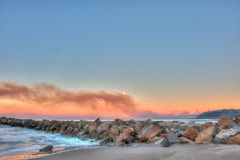 Brush fire in distance pollutes the ocean air. Smoke wafting across the horizon from the hillside fire Stock Photos