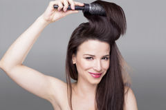 Brush girl. Woman holding a hair brush up in her hair Stock Image