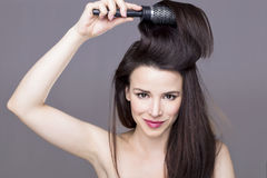 Brush girl. Woman holding brush in her hair Royalty Free Stock Photography