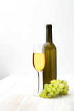 Brush of green grapes, a bottle and glass on white Royalty Free Stock Images