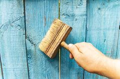 Brush in hand - painting a wooden fence stock images