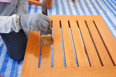 Brush in hand and painting on the wooden furniture Royalty Free Stock Photo