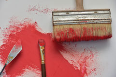 Brush. An image of two brushes and a palette knot against a background of red oil paint Royalty Free Stock Images