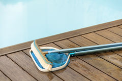 Brush and Leaf Skimmer Beside Swimming Pool royalty free stock images