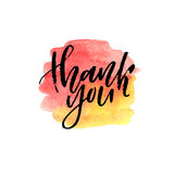 Brush lettering Thank you on watercolor splash in red and yellow colors. Brush ink lettering Thank you on watercolor splash in red and yellow colors Royalty Free Stock Photography