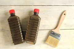A brush lies next to a plastic bottle with stain on an old white vintage wooden plank table. Place for text or logo. Transparent, mordant, solvent, kerosene royalty free stock photo