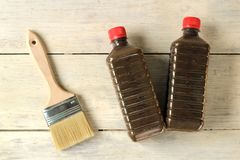 A brush lies next to a plastic bottle with varnish on an old white vintage wooden plank table. Place for text or logo. Transparent, stain, mordant, solvent stock photo