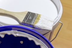 A brush lying on the edge of paint bucket with white paint. stock images