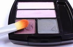 Brush for makeup lying on cosmetic eyeshadow Stock Photos