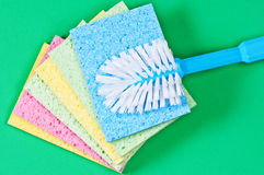 Brush and multi color sponges on green background. Brush and multi color sponges for cleaning on green background Stock Photo