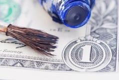 Brush, oilpaint and dollar Stock Photo