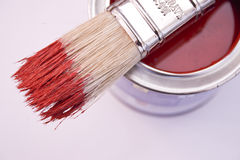 Brush and paint. A can of red paint with a brush on top with a red coloured tip royalty free stock photos