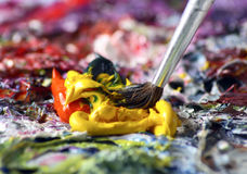 Brush in Paint. Brush daubing into yellow paint, other paint colors all around Stock Photo