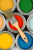 Brush on paint cans. A wooden brush on paint cans of various colors Stock Image