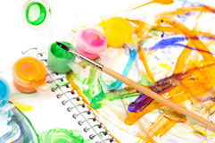 Brush, paint and children's drawing. On white Stock Images