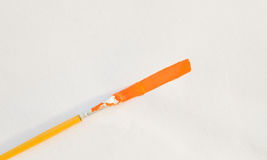 Brush paint of Poster Orange color on white drawing paper. Stock Photography