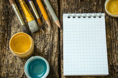 Brush painting, chiseled pencils, gouache paint, notepad on the old wooden table Royalty Free Stock Photos