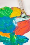 Paints of Different colors and paint brush on white table. The brush and paints of various colors and red and green and yellow and blue are spilled on white Stock Photography