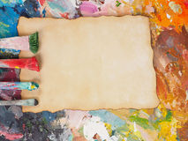 Brush and paper on oil-paint palette for background Royalty Free Stock Photo