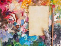Brush and paper on oil-paint palette for background Stock Photos