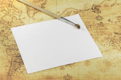 Brush and paper on a old world map Stock Images