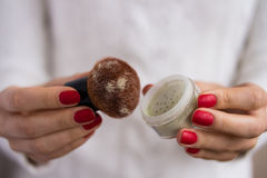 Brush and powder in female hands Stock Photography