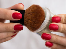 Brush and powder in female hands. With red nails Royalty Free Stock Photography