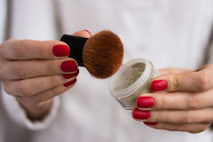 Brush and powder in female hands. With red nails Stock Photography