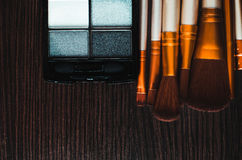 Brush and powdering. Makeup brushes on the table were gold, and powder next Royalty Free Stock Photos