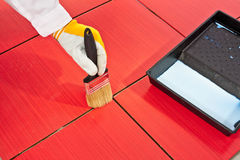 Brush primer grout of red tiles resistant. Hand in yellow glove painting with black brush primer on grout of red tiles resistant Royalty Free Stock Photography