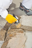 Brush primer grout of stones joint. Worker brush primer grout of stones joint Stock Image