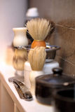 Brush and razor shaving in barber shop Stock Images