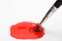 Brush and red color paint. Close up stock photography