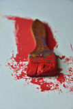Brush with red oil paint. Image of a brush on a background of red oil paint Royalty Free Stock Photos