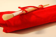 Brush on red wrap. Brush with wooden handle, on a wrap of red fabric royalty free stock photo