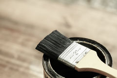 Brush resting on a tin can of protective paint Stock Photography