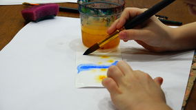 The brush slides on paper drawing with blue and yellow colors.  stock footage