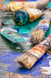 Brush, spatula and color pigments on a palette Stock Photography