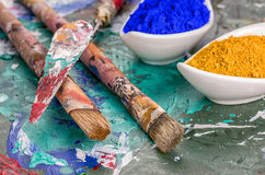 Brush, spatula and color pigments on a wooden palette Stock Photography