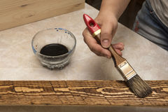 Brush and stain. Decorating the boards with a brush and stain Stock Photos